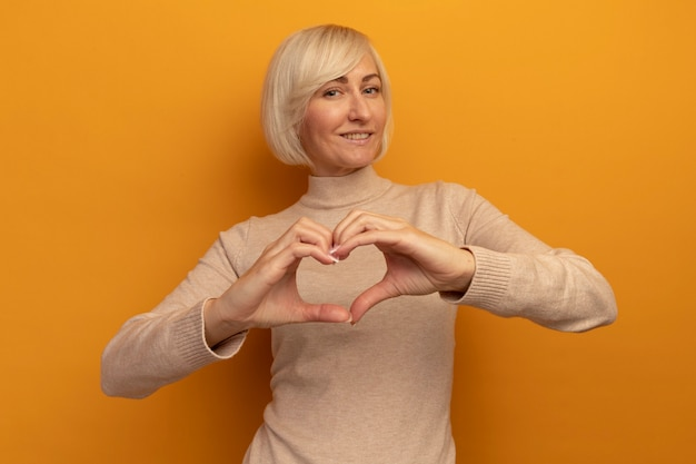 笑顔のきれいな金髪のスラブ女性ジェスチャーハートハンドサイン分離 無料写真