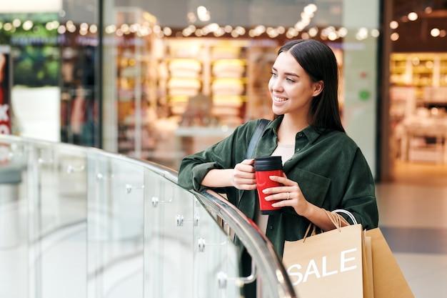 手すりに立って、ショッピングモールのホールで魔法瓶カップから熱いお茶を飲むかわいいブルネットの女の子の笑顔 Premium写真
