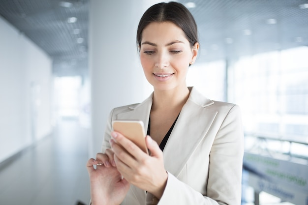 Smiling Pretty Business Lady Using Smartphone Free Photo