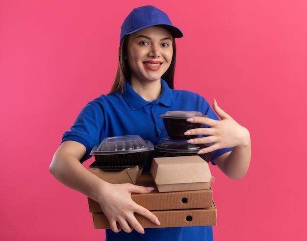 制服を着た笑顔のかわいい配達の女性は、コピースペースとピンクの壁に分離されたピザボックスに食品パッケージとコンテナを保持 無料写真