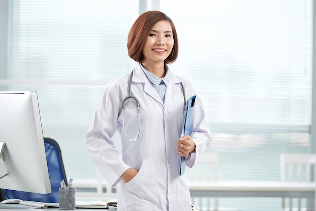Smiling pretty doctor standing in the hospital office with a paper folder Free Photo