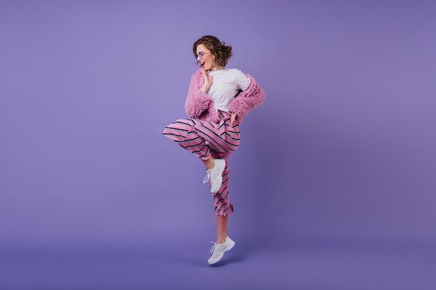 보라색 벽에 한쪽 다리에 물결 모양의 헤어 스타일 서 예쁜 여자를 웃 고. 흰색 스 니 커 즈에서 춤을 밝은 갈색 머리 여성 모델. 무료 사진