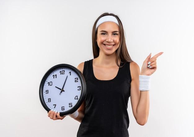 Sorridente ragazza piuttosto sportiva che indossa la fascia e il braccialetto che tiene l'orologio e che indica al lato isolato su spazio bianco Foto Gratuite
