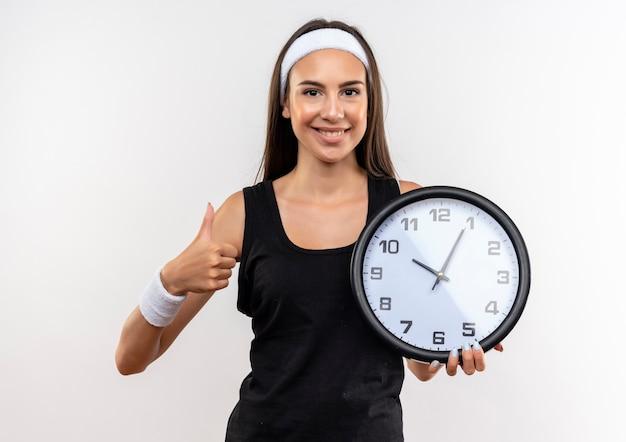 Sorridente ragazza piuttosto sportiva che indossa la fascia e il braccialetto che tiene l'orologio e che mostra il pollice in su isolato su spazio bianco Foto Gratuite