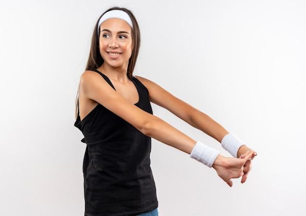 Sorridente ragazza abbastanza sportiva che indossa la fascia e il braccialetto che tengono le mani insieme guardando il lato isolato su uno spazio bianco Foto Gratuite