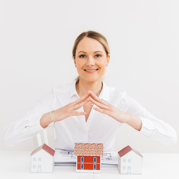 Smiling pretty woman giving security to model house at workplace Free Photo