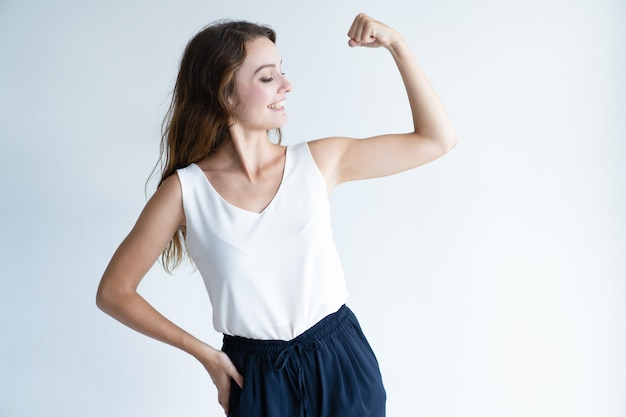 Smiling pretty woman showing her bicep Free Photo