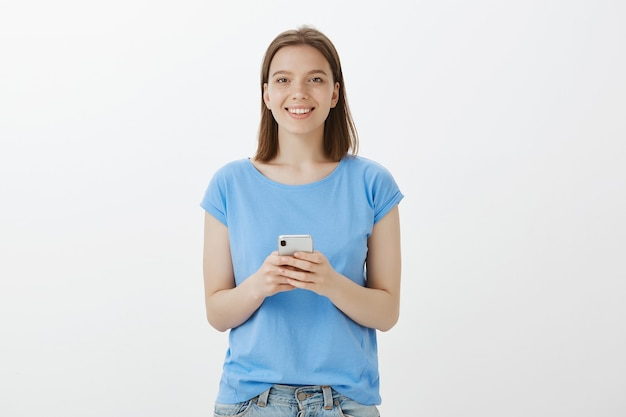 Donna graziosa sorridente che utilizza smartphone, messaggio di testo o applicazione di download Foto Gratuite