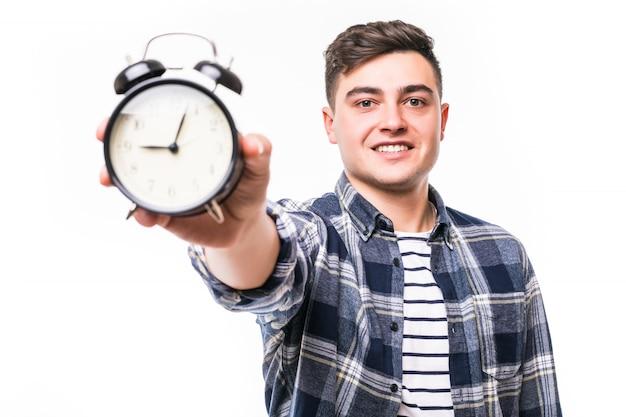 Улыбаясь довольно молодой мальчик, показывая время на черном будильнике Бесплатные Фотографии