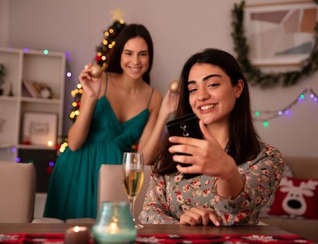웃는 예쁜 젊은 여자는 테이블에 앉아 셀카를 복용하고 집에서 크리스마스 시간을 즐기는 그녀의 친구 뒤에 서있는 유리 공 장식품을 보유하고 있습니다. 무료 사진