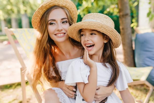 晴れた日に屋外で時間を過ごしながら目をそらしているかなり若い女性と彼女の娘の笑顔。妹と楽しんでいる小さなブルネットの少女のクローズアップの肖像画 無料写真
