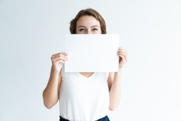 Smiling pretty young woman hiding behind blank sheet of paper Free Photo