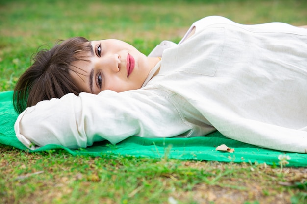 Smiling pretty young woman lying and relaxing on lawn Free Photo