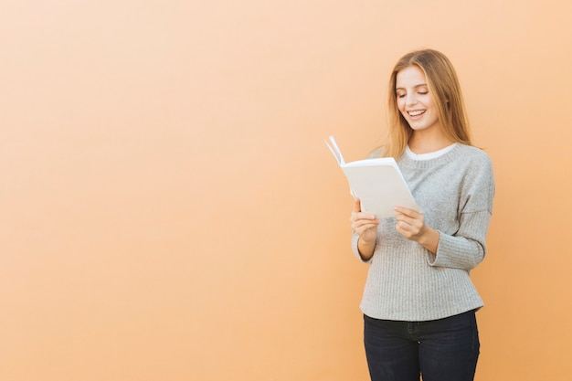 Smiling pretty young woman reading book against colored background Free Photo