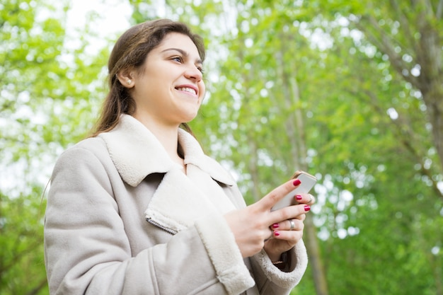 Smiling pretty young woman using smartphone in park Free Photo