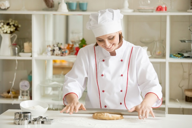 Smiling professional confectioner rolling gingerbread dough Free Photo