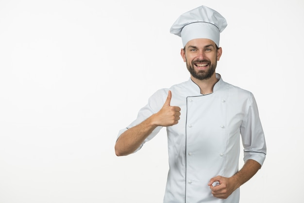 smiling professional cook showing thumb up sign against white