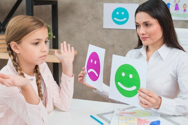 Smiling psychologist showing happy and sad emotion faces cards to the girl child Free Photo