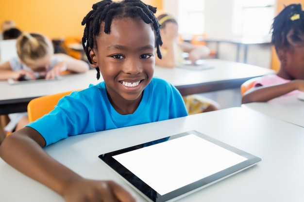 Smiling pupil posing at desk with tablet pc Premium Photo