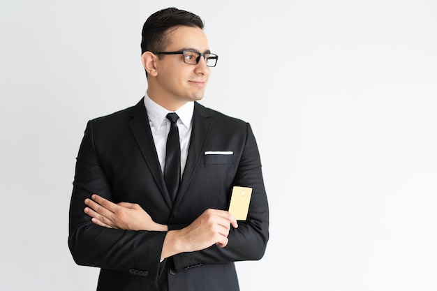 Smiling purposeful young businessman with credit card looking aside. Free Photo