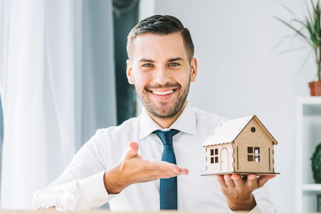 smiling real estate agent demonstrating toy house photo