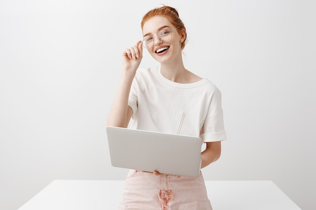 Smiling redhead girl using laptop and looking Free Photo