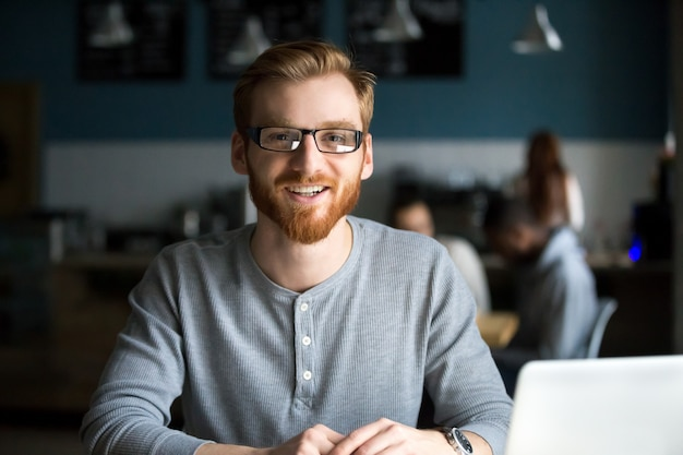 Smiling redhead man with laptop looking at camera in cafe Free Photo