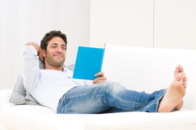 ソファーで横になっている本を読んでリラックスした男の笑顔 Premium写真