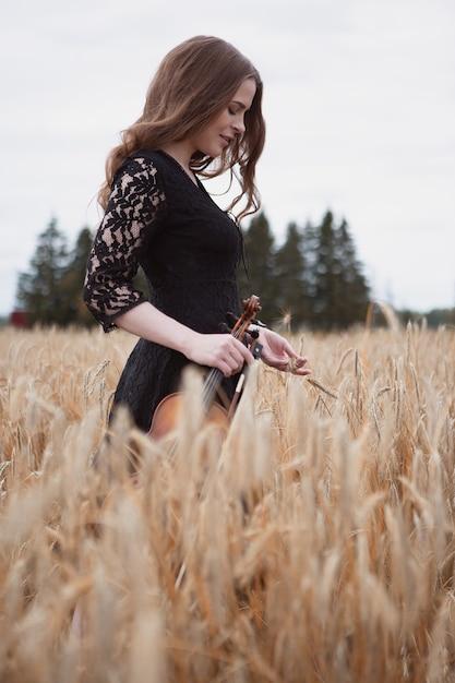 Улыбающаяся романтическая девушка-скрипач на пшеничном поле, в одной руке держа скрипку, а в другой смычок - Premium Фотографии