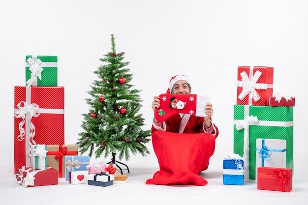 Улыбающийся санта-клаус сидит на земле и поднимает рождественский носок к лицу возле подарков и украшает новогоднюю елку на белом фоне Бесплатные Фотографии