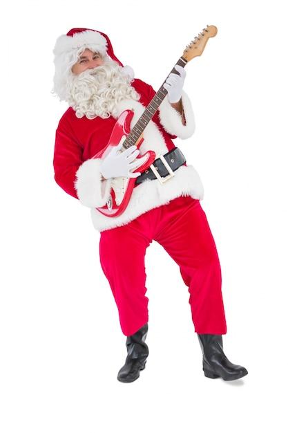 Smiling santa playing electric guitar Premium Photo