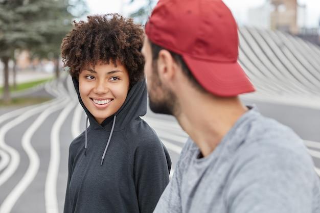 パーカーで満足しているエスニックかわいい女の子の笑顔は、男と楽しい友好的な会話をしています、屋外を歩く 無料写真
