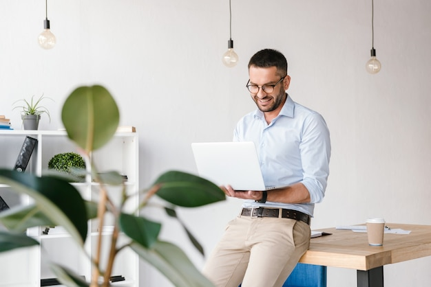 Smiling satisfied man 30s wearing white shirt sitting on table in office, and having business chat on silver laptop Premium Photo