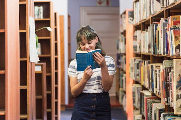 Smiling schoolgirl reading book in library Free Photo