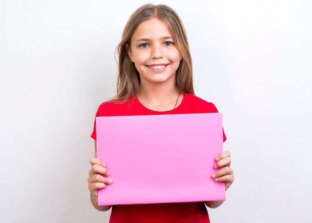 Smiling schoolgirl showing empty copybook Free Photo