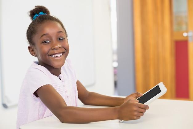 Smiling schoolgirl using digital tablet in classroom at school Premium Photo