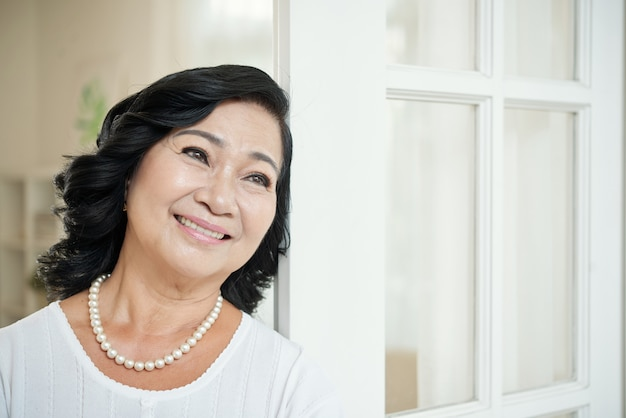 Smiling senior asian woman leaning on door at home and looking away Free Photo