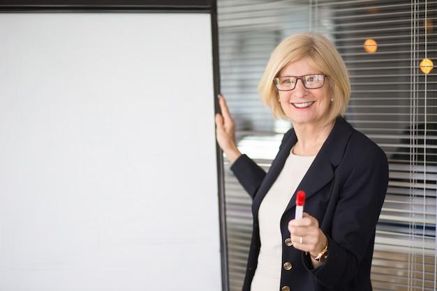 Улыбаясь старший бизнес-леди, обращаясь к аудитории Бесплатные Фотографии