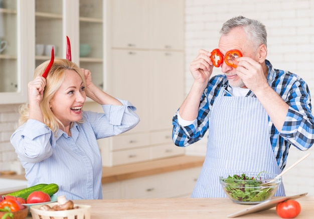 Smiling senior couple making fun with red chili peppers and bell peppers standing in the kitchen Free Photo