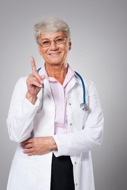 指で指して笑顔の先輩医師 無料写真
