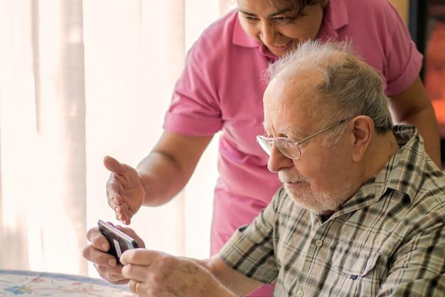 Улыбающийся пожилой мужчина и опекун со смартфоном делают видеозвонок Premium Фотографии
