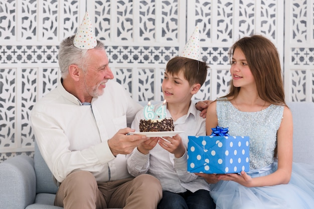 Smiling senior man looking at his grandchildren holding delicious birthday cake and gift box sitting on sofa Free Photo
