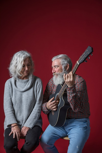 Smiling senior man playing guitar for her wife sitting against red background Free Photo