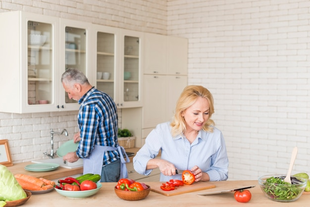 Free Photo   Smiling senior woman cutting the red bell pepper with knife  looking at digital tablet and his husband washing dishes in kitchen sink