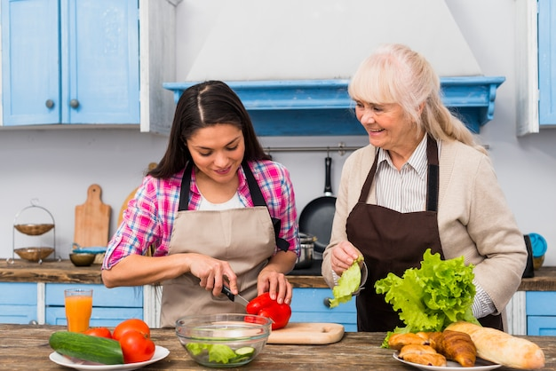 Smiling senior woman looking at daughter cutting vegetable in the kitchen Free Photo