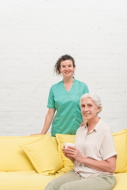 Smiling senior woman sitting on sofa holding coffee cup in front of nurse Free Photo