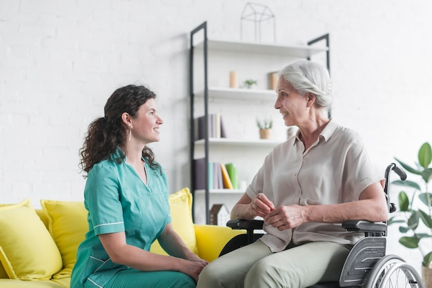 Smiling senior woman sitting on wheel chair looking at female nurse Free Photo
