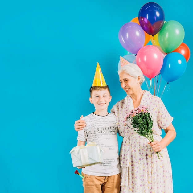 Smiling senior woman standing with grandson holding birthday gift on blue backdrop Free Photo