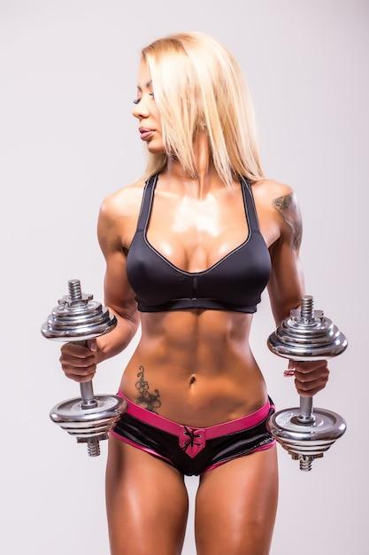 회색에 아령으로 Muscules를 펌핑 섹시 운동 여자 미소 무료 사진