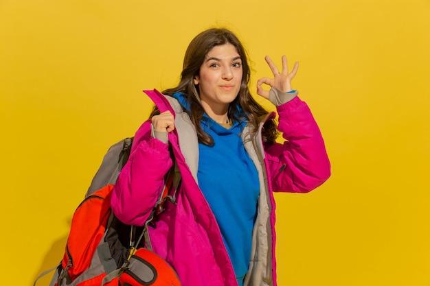 웃고, 멋지게 보여줍니다. 가방과 노란색 스튜디오 배경에 고립 된 쌍안경 쾌활 한 젊은 백인 관광 여자의 초상화. 무료 사진